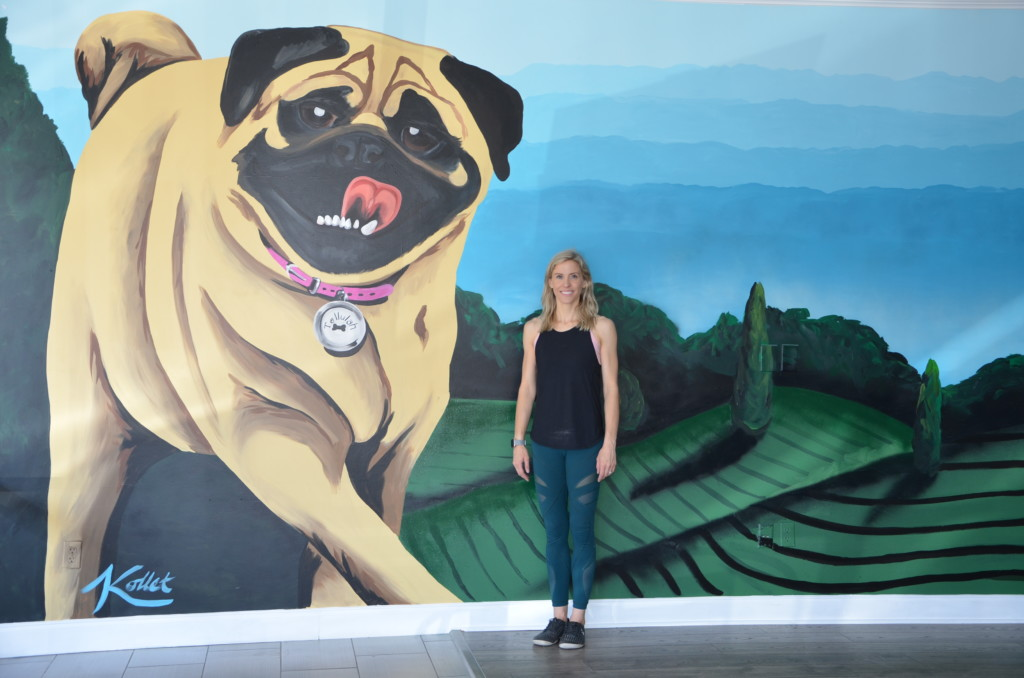 Owner Ashley Guy standing in front of dog wall mural